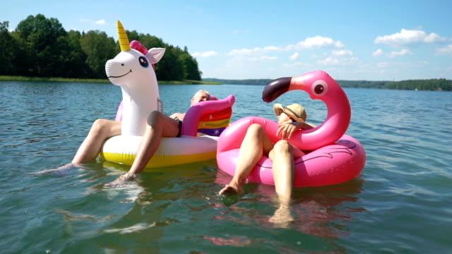 yaşlı çift şişme flamingo ve tek boynuzlu at üzerinde yüzen. - eksantrik stok videoları ve detay görüntü çekimi