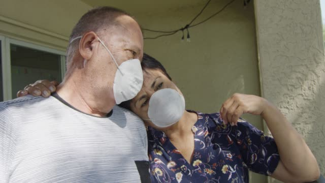 Elderly couple leaning on each other while wearing face masks during quarantine video