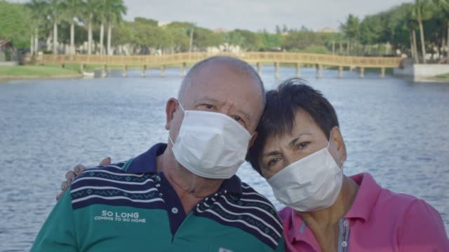 Elderly couple looking at camera while wearing face masks in front of a lake video