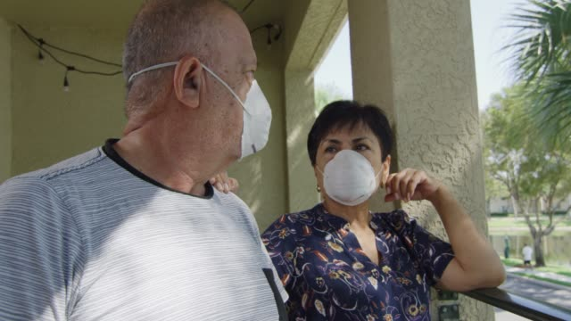 Elderly couple looking at each other wearing face masks during quarantine video