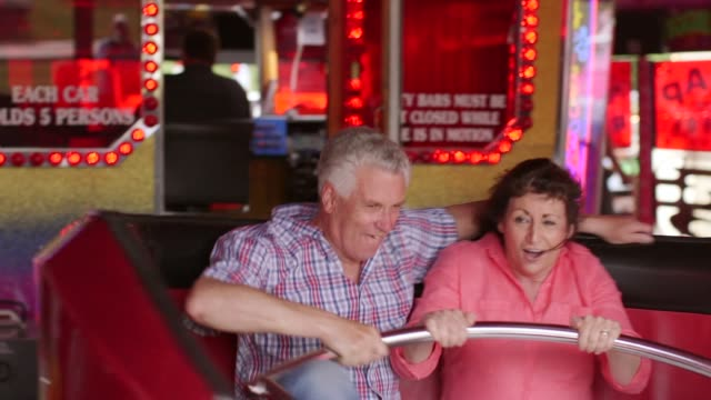 Elderly Couple On Waltzer At Funfair video