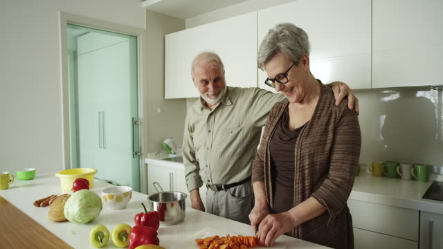 Elderly couple preparing a meal together video