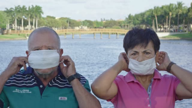 Elderly couple putting face masks on in front of a lake video