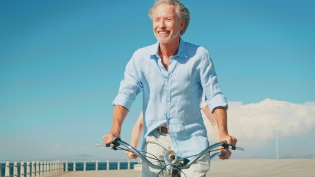 Elderly couple riding tandem bicycle on promenade