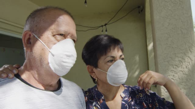 Elderly couple wearing face masks during quarantine, looking worried and sad video