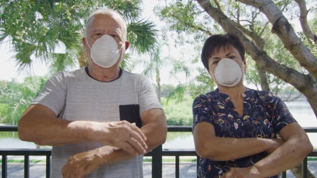Elderly couple with face masks looking at camera during quarantine video