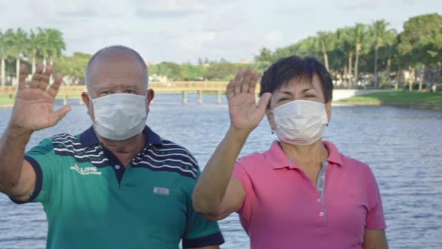 Elderly couple with face masks waving at the camera video
