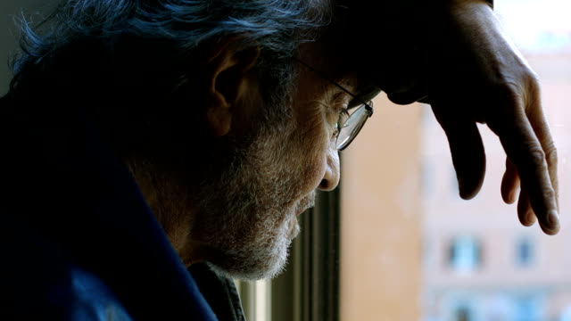 Elderly desperate man  looking out the window video