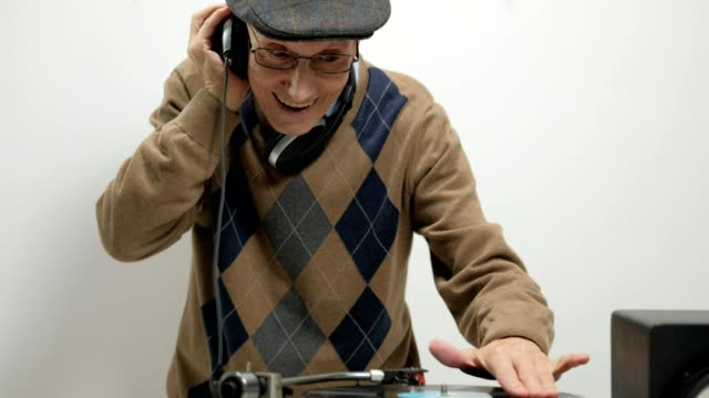 Elderly DJ playing music on a turntable and making a thumb up gesture video