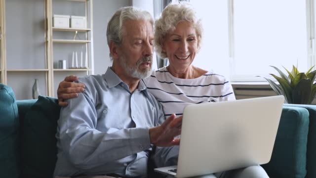 Elderly family grandparents couple talking using laptop sit on sofa