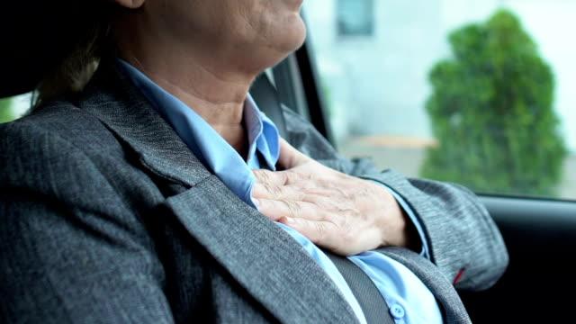 vídeos de stock e filmes b-roll de elderly female driver suffering from pain in chest, risk of heart attack, health - ataque cardíaco
