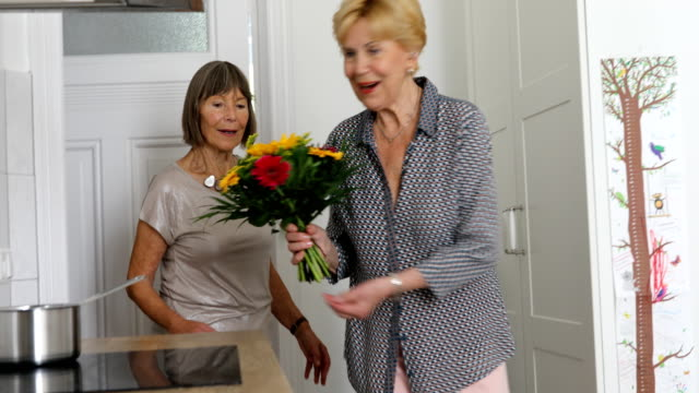 Elderly female friends walking in to kitchen with flowers.