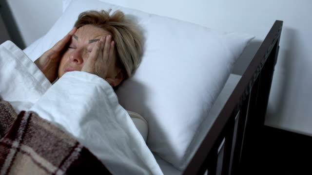 vídeos y material grabado en eventos de stock de paciente anciana masajeando templos, sufriendo una terrible migraña en la cama de enfermos - geriatría