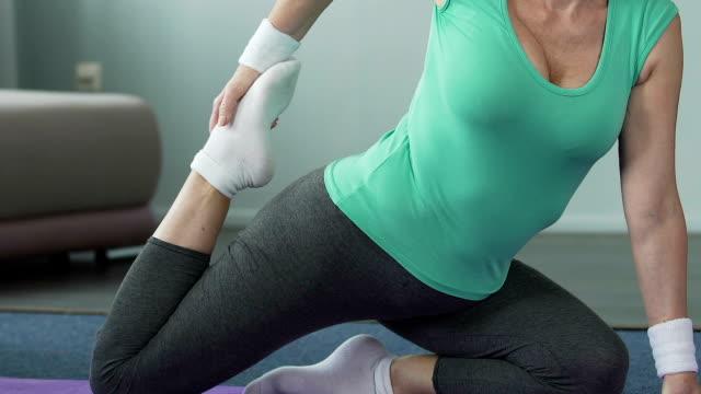 Elderly female sitting on yoga mat in half-splits, turning back to stretch leg video