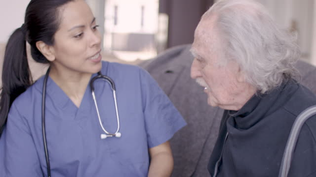 vídeos y material grabado en eventos de stock de anciano caballero con enfermera durante la visita de cuidado en el hogar - servicios sociales