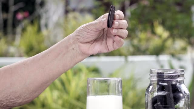 elderly hand dipping and stir a chocolate cookie in milk glass - immergere video stock e b–roll