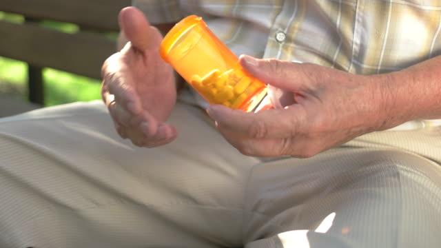Elderly hand holds pills. video
