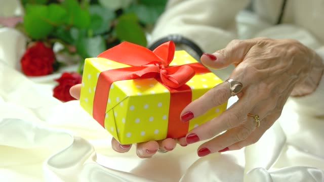 elderly hands with gift box, slow motion. - nastro per capelli video stock e b–roll