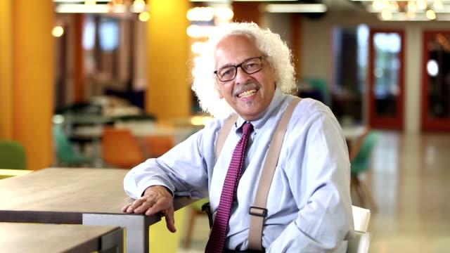 Elderly Hispanic businessman smiling, slaps table