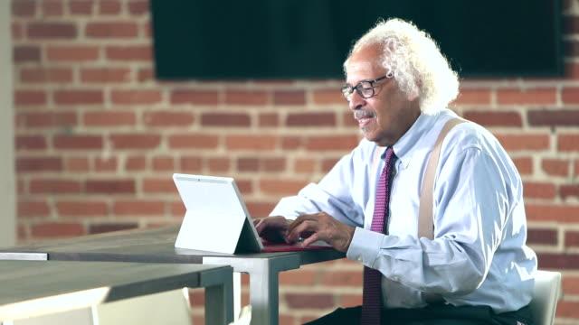Elderly Hispanic businessman typing on computer