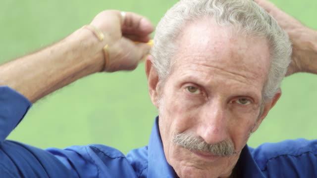 Elderly hispanic man looking and smiling at camera, brushing hair video