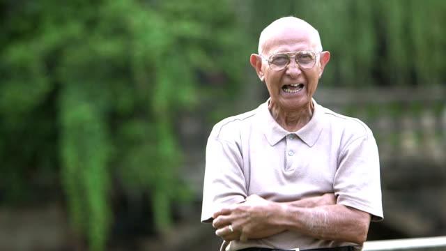 Elderly Hispanic man standing in the park video