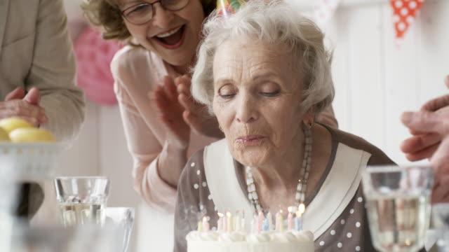 ältere dame geburtstagskerzen ausblasen - geburtstag stock-videos und b-roll-filmmaterial