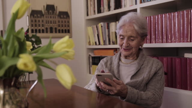 Elderly lady having a video call greets the family saying bye bye to smartphone Elderly lady holding smartphone having a video call  greets the family saying bye bye on the phone sitting in her home with library in background and tulips flowers on the table, italian home interior. Parallax shot zoom call stock videos & royalty-free footage