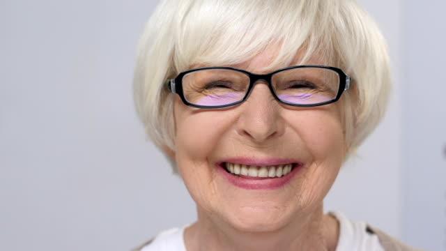пожилая дама в очках счастливо улыбается в камеру, здравоохранение, обследование - близко к стоковые видео и кадры b-roll