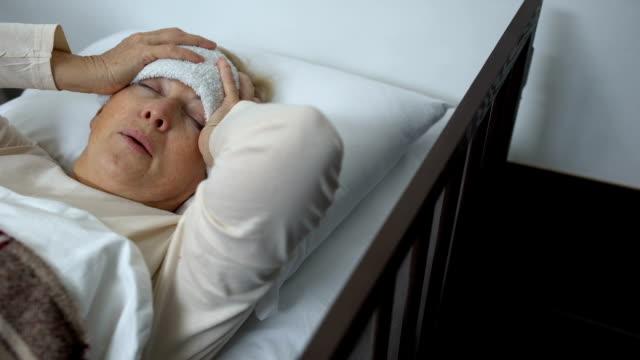 vídeos y material grabado en eventos de stock de anciana acostada en la cama con la frente compresa y sufriendo dolor de cabeza terrible - geriatría