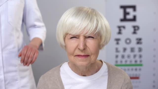 vidéos et rushes de vieille dame visitant l'optométriste amical, contrôlant la vision, le risque de cataracte - examen ophtalmologique