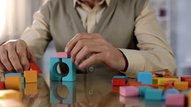 äldre manliga gör hus färgade träkuber, koncentrations övning, terapi - minne bildbanksvideor och videomaterial från bakom kulisserna