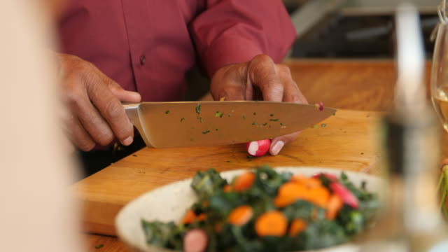 vídeos de stock, filmes e b-roll de homem idoso que adiciona o radish na salada em casa - vegetarian meal