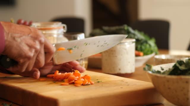 vídeos de stock, filmes e b-roll de homem idoso que adiciona o vegetal na salada em casa - vegetarian meal
