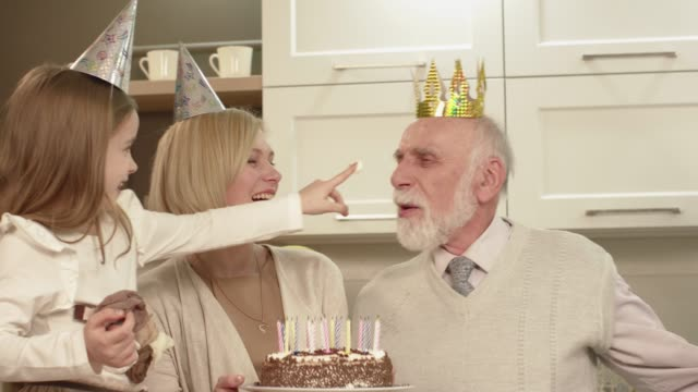 elderly man blows out candles on the cake. - figura femminile video stock e b–roll