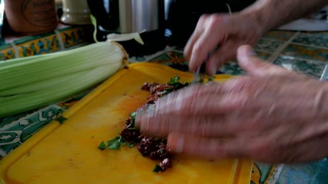 vídeos y material grabado en eventos de stock de un anciano corta perejil fresco con hígado crudo de una tabla de cortar con un cuchillo - pascua judía