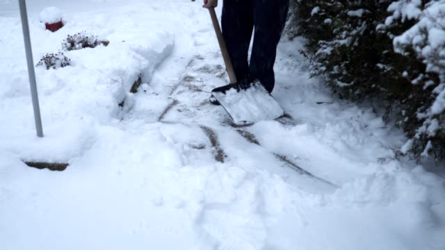 Elderly man cleaning the snow from footpath in his front yard