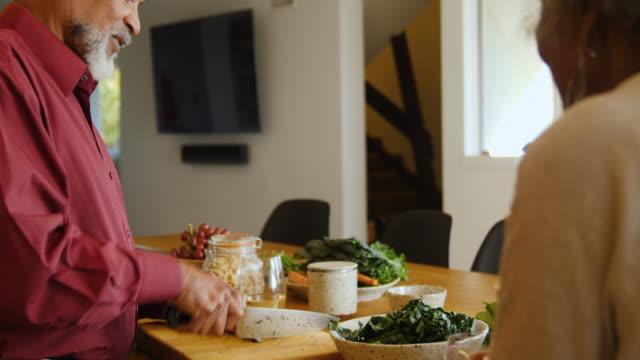 vídeos de stock, filmes e b-roll de o homem idoso que corta a cenoura ao fazer o alimento do vegan - vegetarian meal