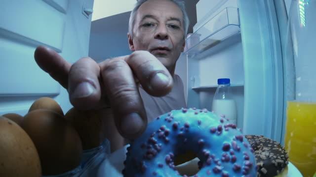 stockvideo's en b-roll-footage met bejaarde die smakelijke donut laat bij nacht eet - ongezond leven