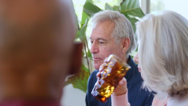 vídeos de stock, filmes e b-roll de o homem idoso que alimenta o pão à esposa no partido da casa - vegetarian meal