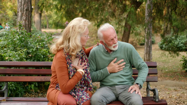 vídeos de stock e filmes b-roll de elderly man having chest pains or heart attack in the park - miocárdio