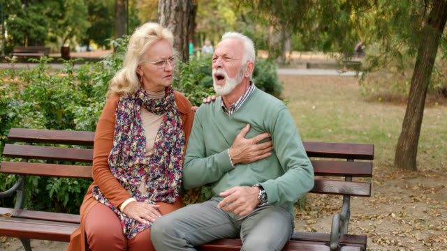 vídeos de stock e filmes b-roll de elderly man having chest pains or heart attack in the park - ataque cardíaco