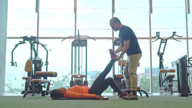 stockvideo's en b-roll-footage met bejaarde man helpt zijn sportschool vriend strekken zijn benen op te warmen - fitnessleraar