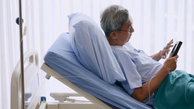 Elderly man holding photo frame with picture of family while lying on patient bed video
