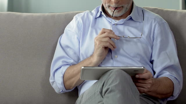 Elderly man holding tablet on lap, planning and booking retirement trip, closeup video