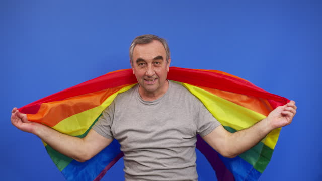 Elderly man holding with lgbt pride flag. Alone. One. covering LGBT flag. LGBT flag on blue background.