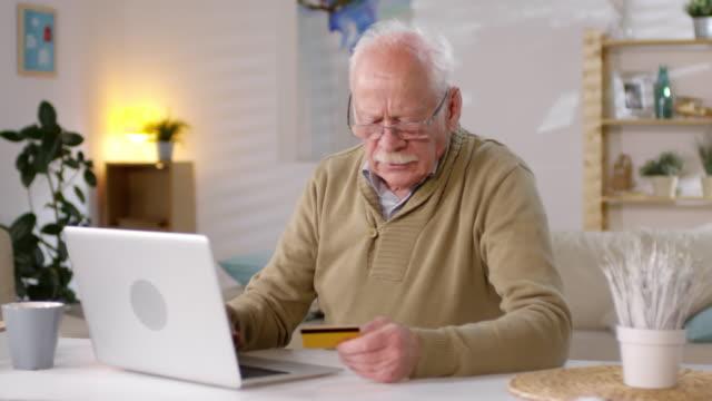 elderly man in glasses shopping online - credit card filmów i materiałów b-roll