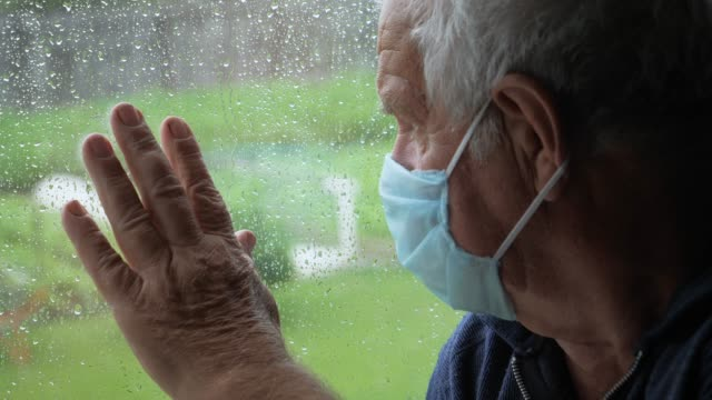 elderly man in medical mask looks out the window and puts his hand on the glass - hand on glass covid video stock e b–roll