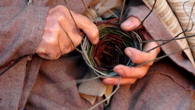 elderly man is weaving a basket with gorse