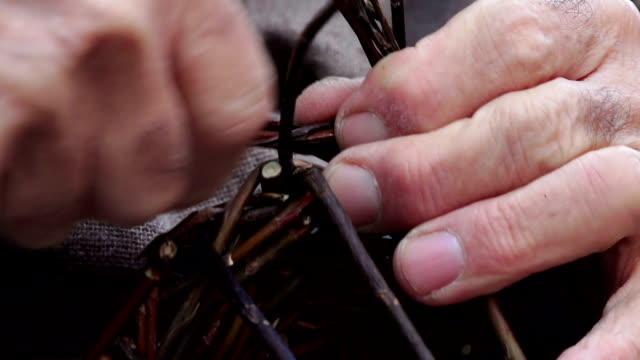 elderly man is weaving a basket with gorse video
